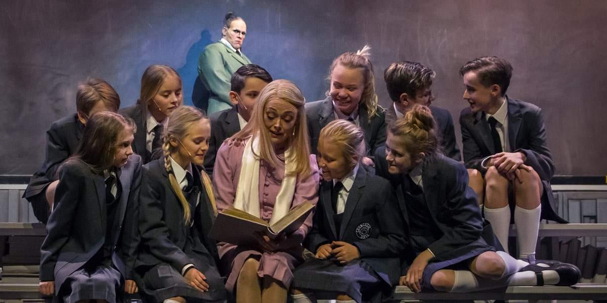 Fröken Honey med sin klass och Rektor Trunchbull i bakgrunden.